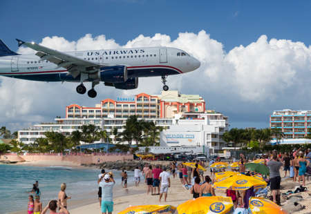 approached: PRINCESS JULIANA AIRPORT, ST MARTIN -  NOVEMBER 1: US Airways flight lands over Maho beach on November 1, 2012. The 2300m runway is approached over the sea.