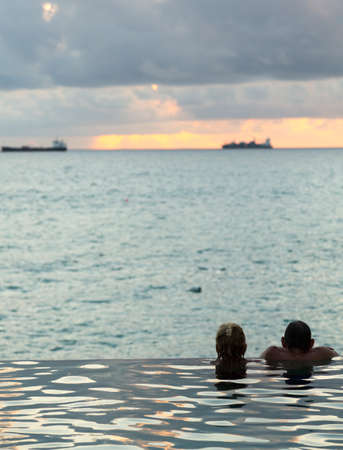 Silhouette of couple heads at the edge of infinity swimming pool overlooking ocean at sunset photo