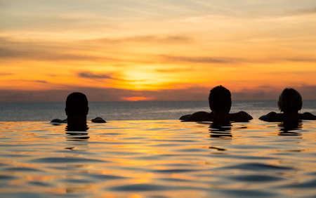 夕暮れの海を一望できるインフィニティ スイミング プールの端に人々 の頭のシルエット