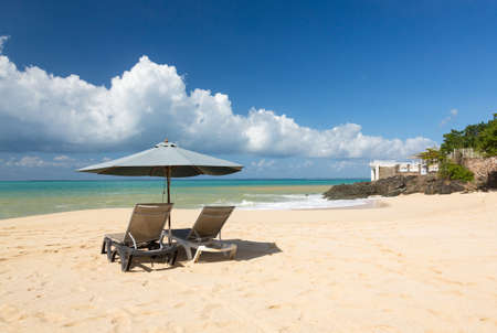 Reclining beach loungers and umbrella on Baie Rouge St Martin Caribbean photo