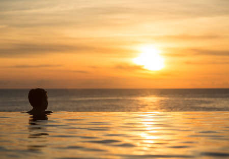 Silhouette of person head at the edge of infinity swimming pool overlooking ocean at sunset