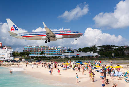 PRINCESS JULIANA AIRPORT, ST MARTIN -  NOVEMBER 1: American Airlines flight lands over Maho beach on November 1, 2012. The 2300m runway is approached over the sea.