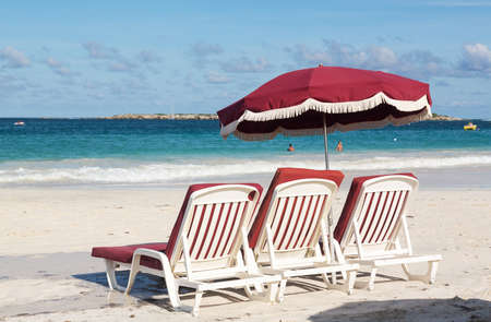 Three white plastic beach loungers and umbrella on Orient Beach St Martin photo