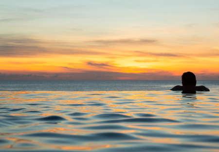 夕暮れの海を一望できるインフィニティ スイミング プールの端に人の頭のシルエット