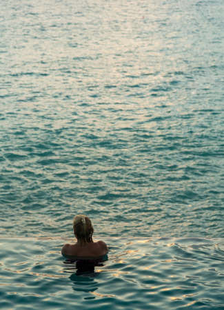 Silhouette of person head at the edge of infinity swimming pool overlooking ocean at sunset photo