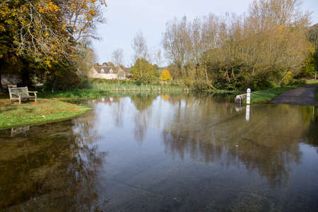 Seat overlooking a deep river at road ford on Shill Brook at Shilton Oxfordshire Stock Photo - 16449577
