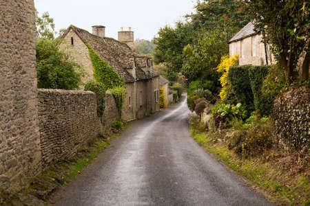 Úzká ulička v vilalge z Minster Lovell v Cotswolds s kamennými domky