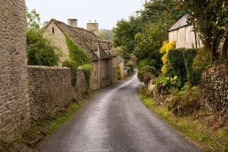 old english: Narrow lane in vilalge of Minster Lovell in Cotswolds with stone cottages