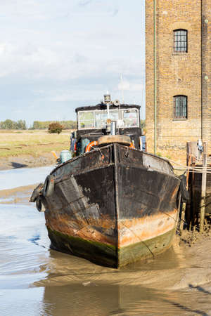 beached: Thames sailing ship or houseboat by dock in Faversham Kent UK Stock Photo