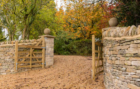 cotswold: Stylish wooden gates across gravel drive and cotswold stone wall Stock Photo