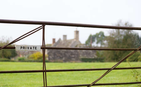 White painted private sign on iron metal farm gate in field with farm cottage in distance photo