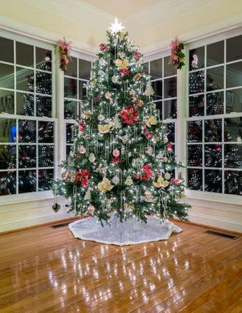 木製の床に反射してライトである近代的な家で飾られたクリスマス クリスマス ツリー