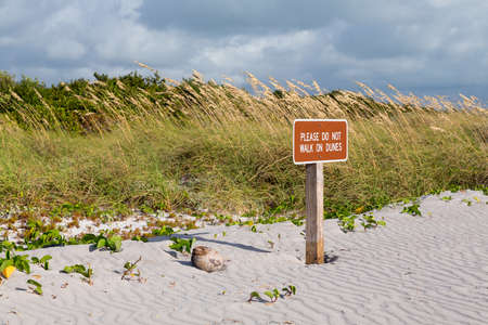 Please do not walk on dunes sign on beach in state park Key Biscayne Florida