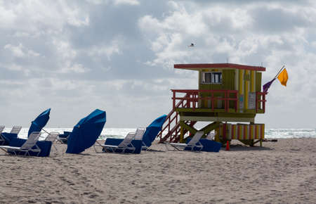 lifeguard tower: Yellow and green lifeguard station on Miami beach Florida with beach umbrellas and recliners Stock Photo