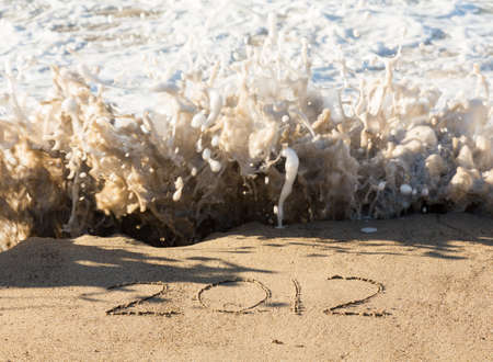 Calendar concept of 2012 written in sand on beach being covered by surf and waves Stock Photo - 16999247
