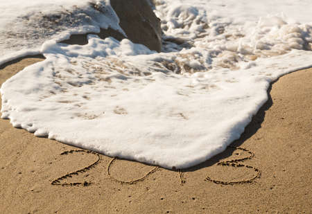 Calendar concept of 2013 written in sand on beach being covered by surf and waves