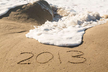 Calendar concept of 2013 written in sand on beach being covered by surf and waves Stock Photo - 16999255