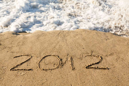 Calendar concept of 2012 written in sand on beach being covered by surf and waves Stock Photo - 16999314