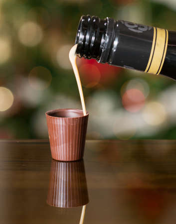 Irish cream milky liqueur being poured into chocolate shot glass with christmas tree photo