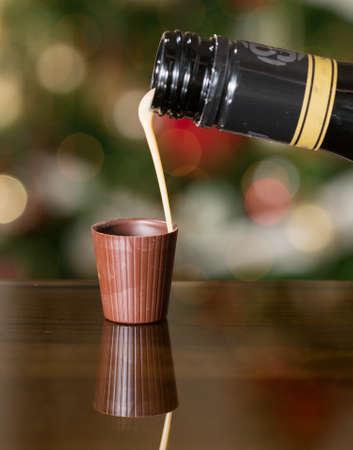 irish christmas: Irish cream milky liqueur being poured into chocolate shot glass with christmas tree Stock Photo