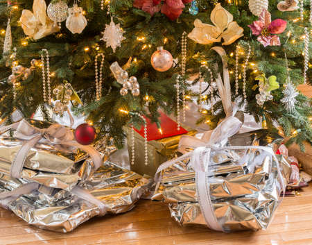 Wrapped presents in silver paper and ribbons underneath Christmas tree on wooden floor Stock Photo - 17070399
