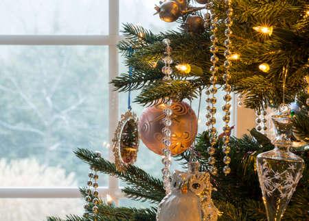 Macro-opname van de kerstboom decoraties op binnen-boom als sneeuw valt buiten venster