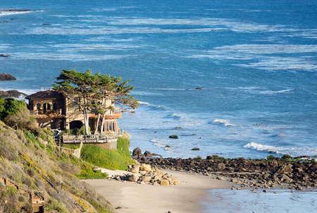 overlook: Modern houses overlook ocean and waves by La Piedra state beach in Malibu California