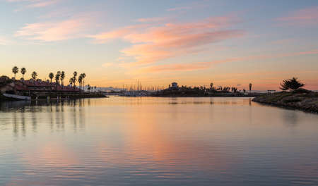 timeshare: Sunrise over timeshare development by water in Ventura California with modern homes and yachts boats Stock Photo