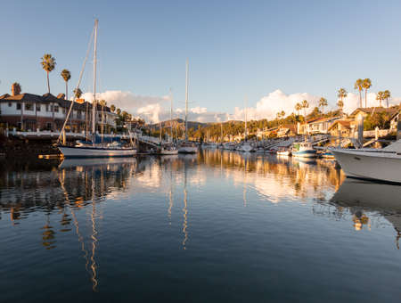 Sunset over residential development by water in Ventura California with modern homes and yachts boats photo
