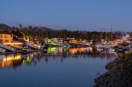 houseboat: Sunset over residential development by water in Ventura California with modern homes and yachts boats Stock Photo