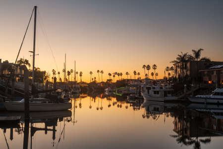 ca: Sunset over residential development by water in Ventura California with modern homes and yachts boats Stock Photo