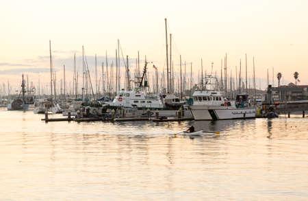 Rowing boat and yachts in harbor at Ventura at dawn as sun is rising photo