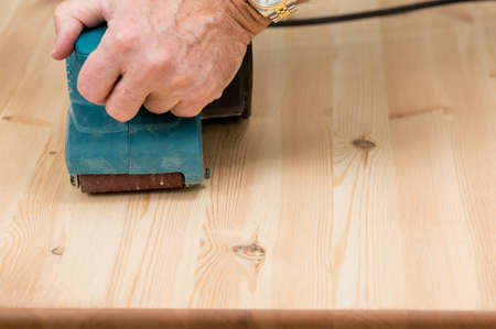 Man holding a belt sander on pine floor or table sanding surface photo