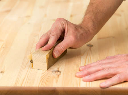 table surface: Man holding sanding block on pine floor or table sanding surface