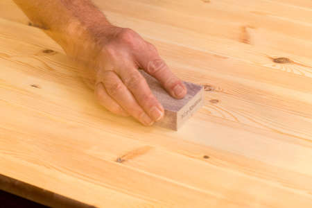 sandpaper: Man rubbing sanding block on pine floor or table with ghosting to suggest movement