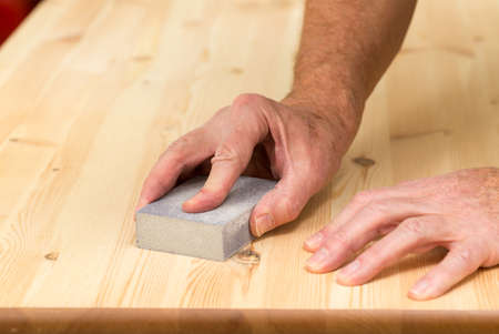 Man holding sanding block on pine floor or table sanding surface