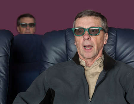 Senior male with shocked expression watching movie in home theater in 3d glasses photo