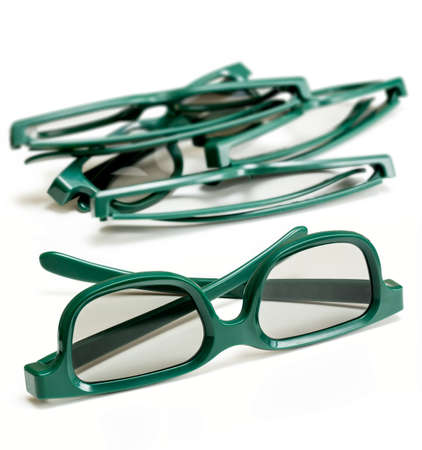 Pair of green 3d polarized glasses for watching 3-d movies in cinema isolated against white with stack of used specs in background photo