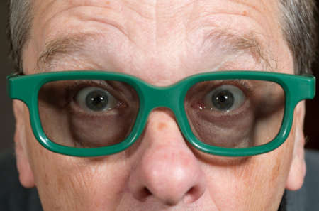 tight focus: Senior male with shocked expression watching movie in 3d glasses with tight focus on face and eyes Stock Photo