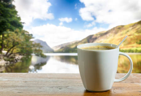 coffee table: Coffee in white pottery cup on old wooden table with blurred image of lake district in England as background Stock Photo