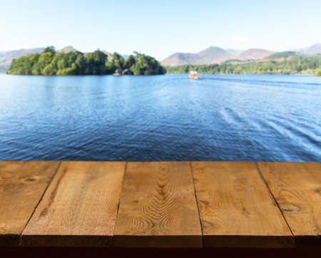 Wood pier or walkway or an old wooden table with blurred image of lake district in England as background photo