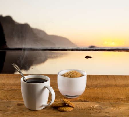snack: Coffee in white pottery cup on old wooden table with blurred image of kauai coast ocean at sunset or sunrise