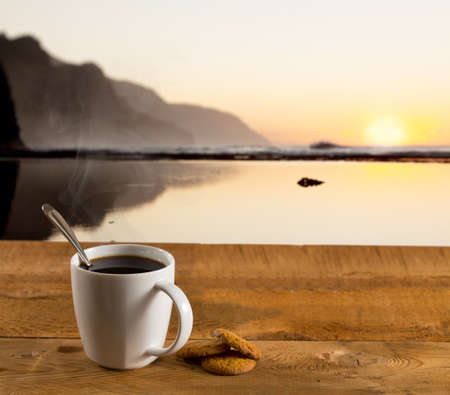 Coffee in white pottery cup on old wooden table with blurred image of kauai coast ocean at sunset or sunrise