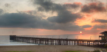 california coast: Pier at Ventura coast in California as the sun is setting over calm Pacific ocean Stock Photo