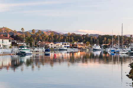 Sunrise at residential development by water in Ventura California with modern homes and yachts boats