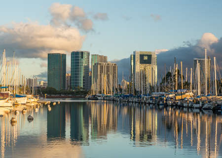 honolulu: Yachts line harbor at Ala Moana near Waikiki Oahu Hawaii with reflections of office and hotel buildings in still water Stock Photo