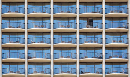 odd one out: Pattern of hotel room balconies in modern building with one patio door open