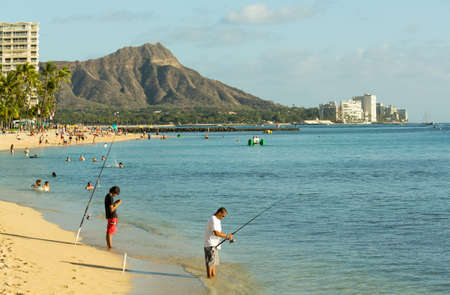 WAIKIKI, HI - JANUARY 20: Fishermen fishing off busy Hawaii beach on 20 January 2012. The Waikiki Beach restoration project was completed early 2012.