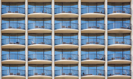 Pattern of hotel room balconies in modern building with all door closed and regular photo