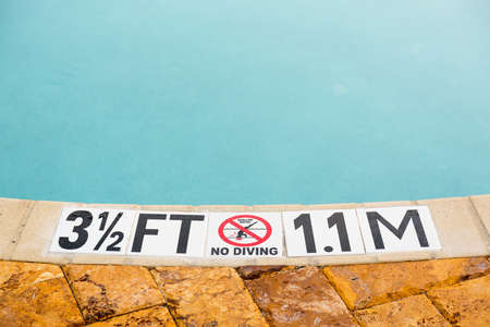 Sign showing 3.5 ft depth on edge of blue swimming pool with no diving 스톡 콘텐츠